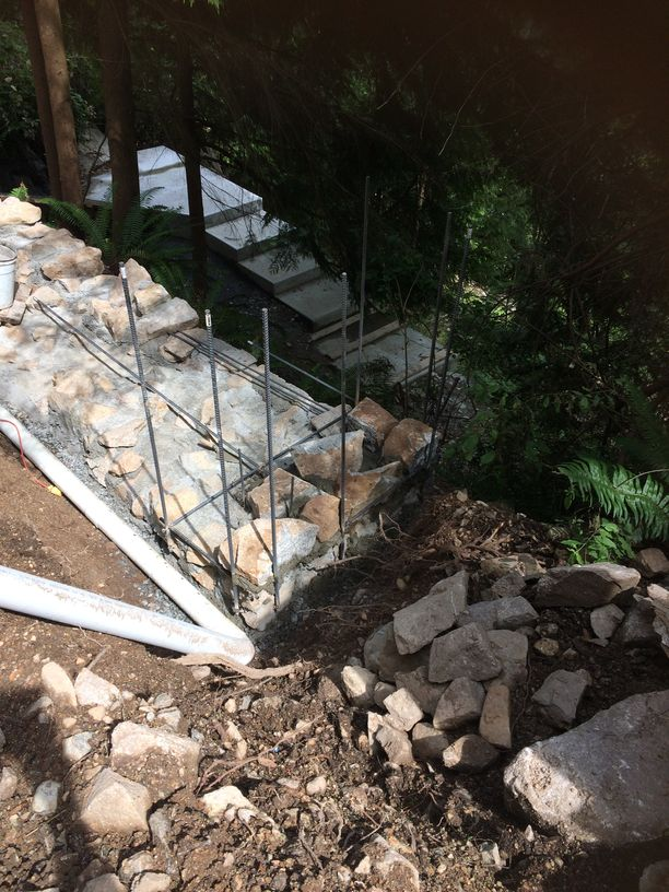 Installing rocks into a retaining wall in Vancouver