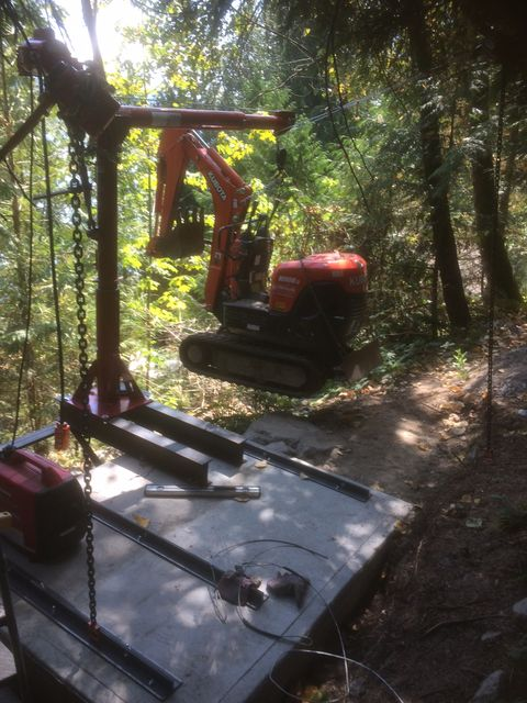 Handyman lifting a mini excavator with removable crane in Hope, BC