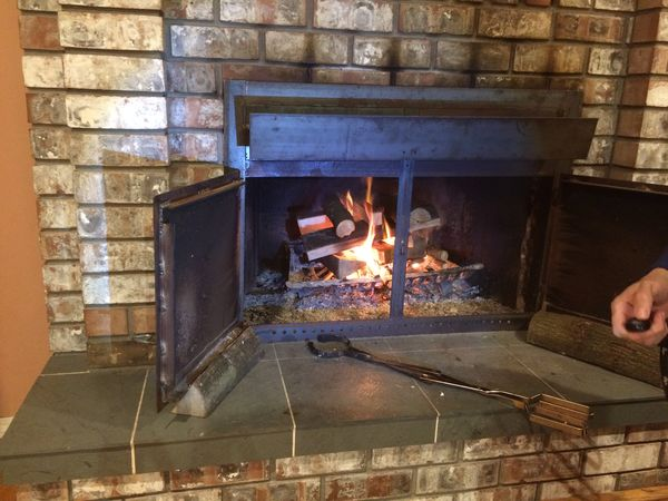 Biger firewood logs added to fireplace fire